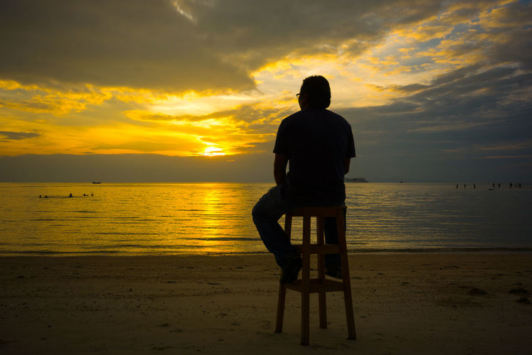 SILHOUETTE MAN SITTING ON WOODEN CHAIR LOOKING OUT SUNSET SKY TWILIGHT SCENIC ,DARK CLOUD AND SHINING LIGHT REFLECTING ON WATER IN BACKGROUND Beach Beauty In Nature Cloud - Sky Full Length Horizon Over Water Idyllic Men Nature One Person Outdoors People Real People Rear View Relaxation Sand Scenics Sea Silhouette Silhouette Photography Sitting Sky Sunset Tranquil Scene Tranquility Water