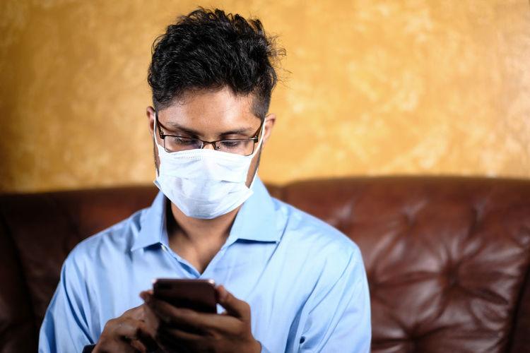 Man wearing flu mask using smart phone sitting on sofa