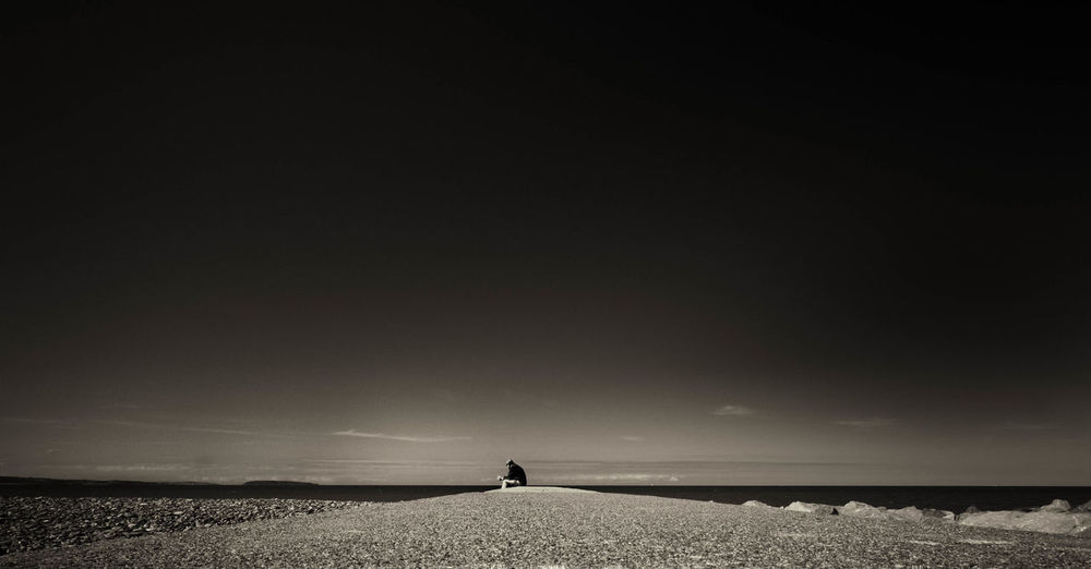 Distant View Of Man Sitting By Sea Shore Against Sky