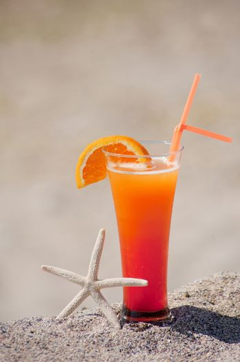 Close-Up Of Orange Juice On Sand
