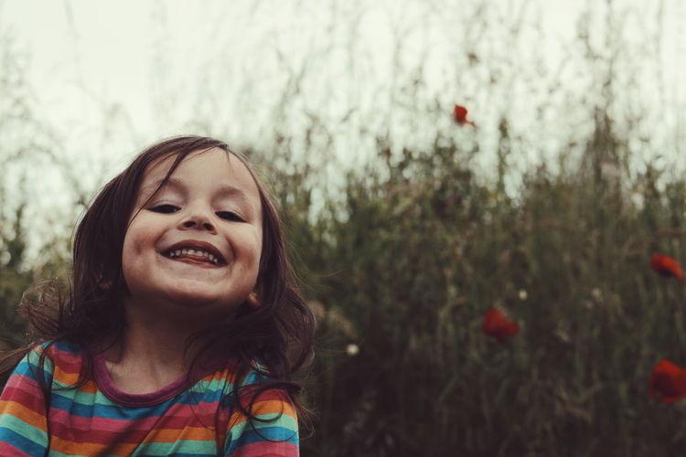 Close-up portrait of girl smiling against plants