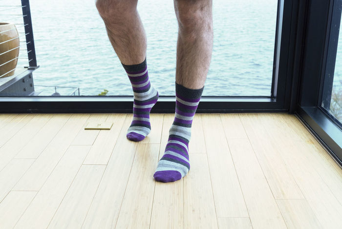 Mans legs showing him wearing striped socks standing by sea view window horizontal landscape. Adult Bare Dating Relationship Adult Affair Cheating Close-up Day Feet Hairy  Human Body Part Human Leg Indoors  Legs Low Section Male Masculine Morning After One Person People Purple Real People Socks Striped