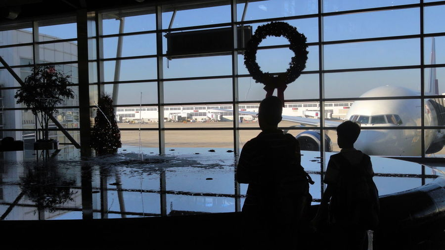 Airport Terminal Boys Christmas Christmas Garland City City Life Coming Home For Christmas Detroit Airport Fountain Glass Glass - Material Indoors  Leisure Activity Lifestyles Looking Through Window Men Person Plane Silhouette Sky Standing The Culture Of The Holidays Transparent Waiting For The Flight Window Connected By Travel