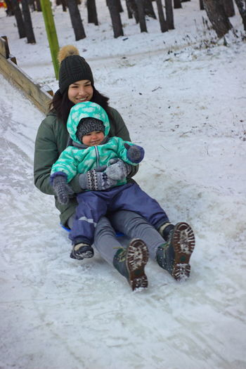 Mother and toddler daughter tobogganing on snow covered field