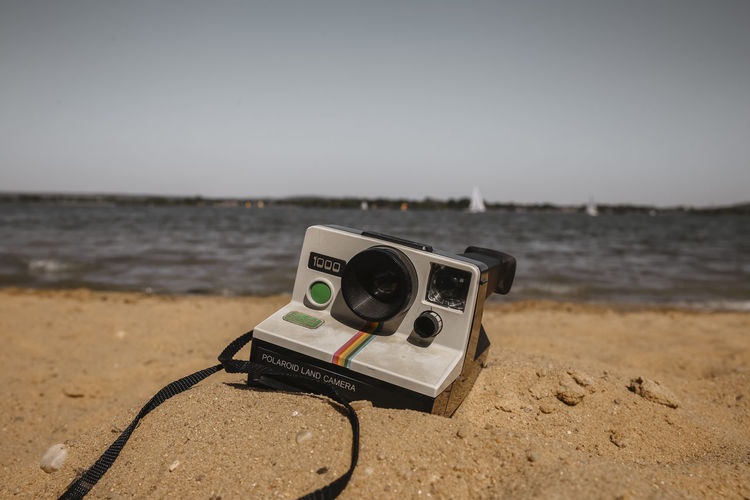 // time is temporary // Beach Beachphotography Camera - Photographic Equipment Close-up Day Digital Camera Focus On Foreground Horizon Instagram Land Nature No People Old Outdoors Photography Themes Polaroid Retro Styled Sand Sea Sky Technology Time Tranquility Vintage Water The Great Outdoors - 2018 EyeEm Awards The Traveler - 2018 EyeEm Awards Summer Sports