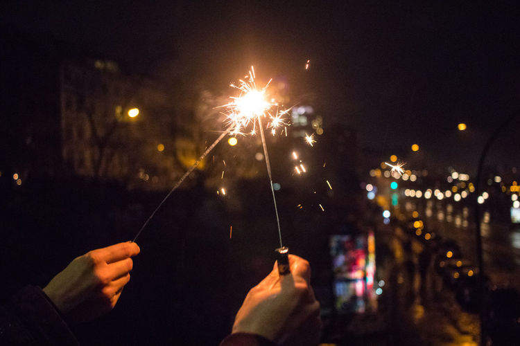 Cropped hands holding illuminated sparklers at night