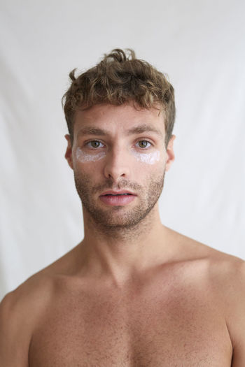 Portrait of shirtless man against white background