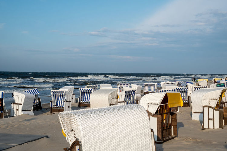 Chairs on table at beach against sky