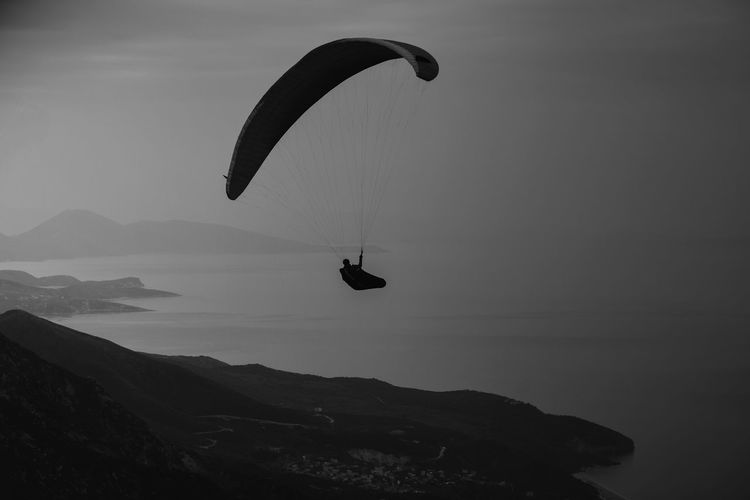 Silhouette person paragliding against sky
