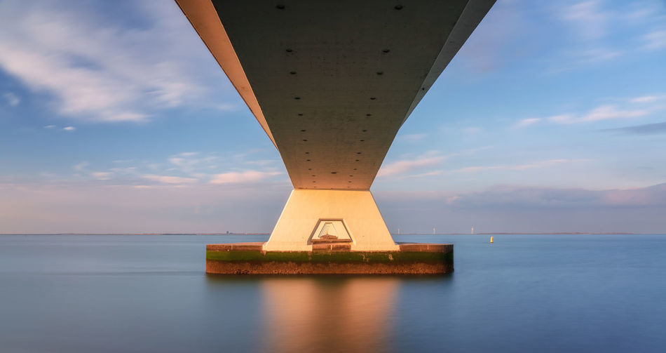 Underneath the Zeeland bridge, Netherlands Sky Water Cloud - Sky Sea Built Structure Horizon Over Water Waterfront Horizon Scenics - Nature Architecture No People Tranquility Beauty In Nature Tranquil Scene Transportation Bridge Bridge - Man Made Structure Outdoors Architectural Column Zeeland  Nederland Holland Zeelandbrug Zeeland Bridge Sunshine Sunset Long Exposure