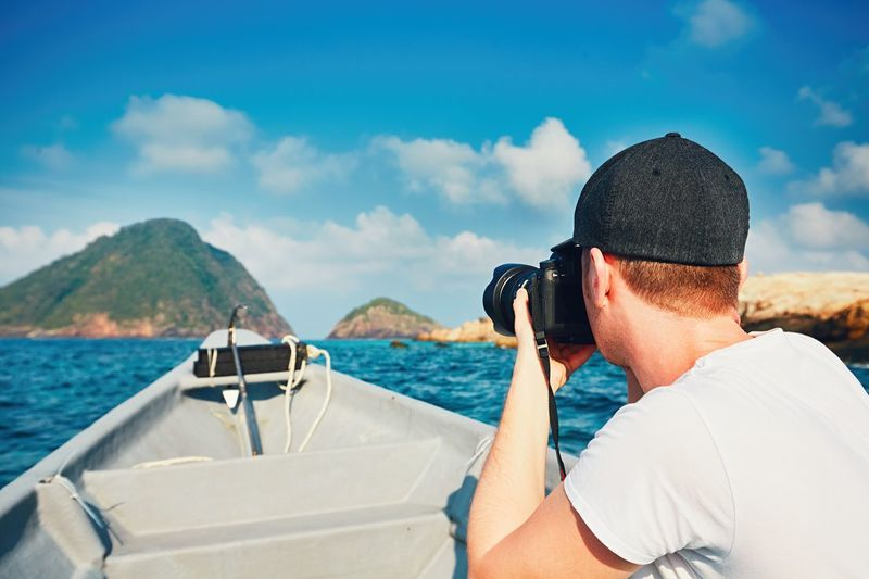 Side View Of Man Photographing While Traveling In Boat On Sea Against Blue Sky