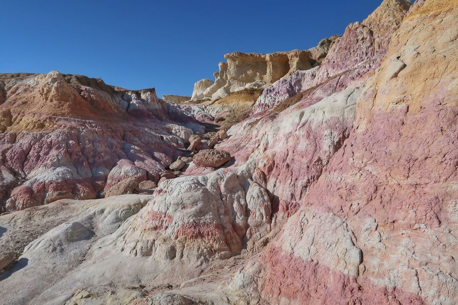 Landscape of pink, white and yellow rock formations in Paint Mines Interpretive Park Unusual View Colorado Paint Mines Interpretive Park Colorful Rocks Sky Nature Mountain Rock Beauty In Nature Scenics - Nature Clear Sky Rock Formation Tranquil Scene Rock - Object Sunlight Land Low Angle View Solid Day Environment Landscape No People Mountain Range Tranquility