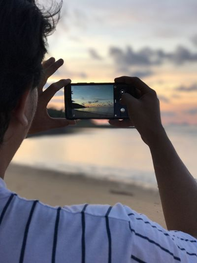 Rear View Of Man Photographing Through Smart Phone At Beach During Sunset