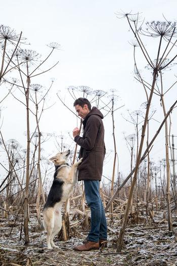 Man standing by dog on land