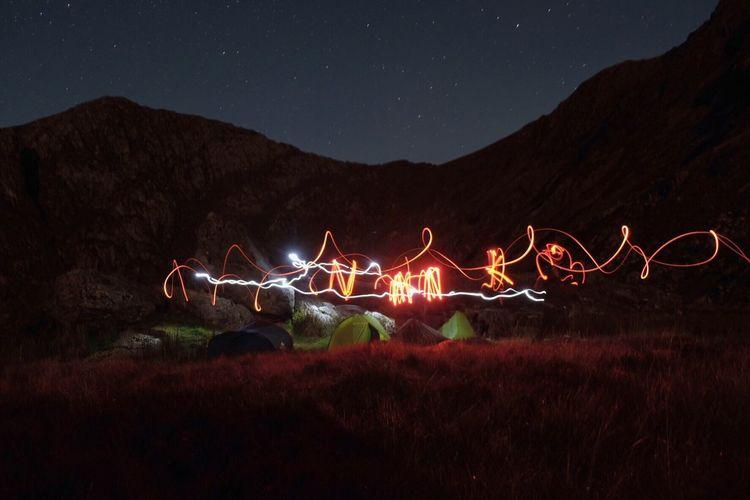 Illuminated light trails on field against sky at night