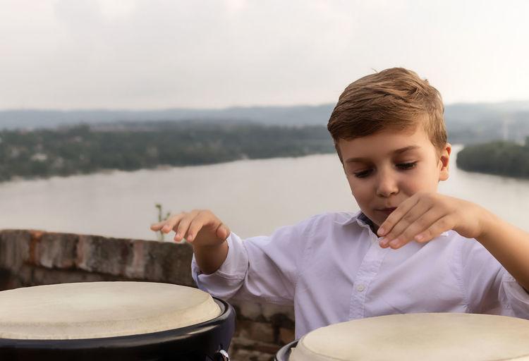 Little drummer playing bongos at riverside.