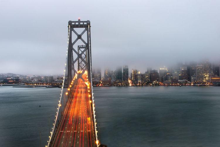 Illuminated oakland bay bridge and building at dusk