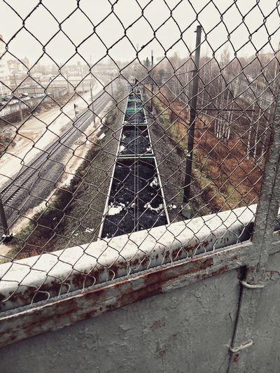 Railroad tracks seen through chainlink fence