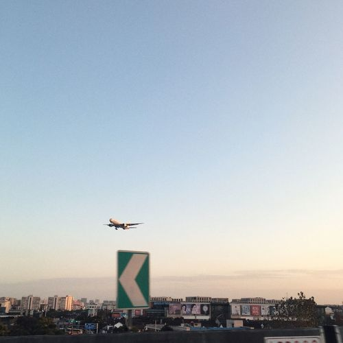 Airplane flying over city against sky