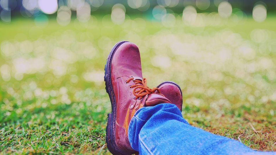 """People always miss you when you look or when you are doing good"". Person Low Section Shoe Relaxation Personal Perspective Grass Lifestyles Human Foot Footwear Field Leisure Activity Close-up Meadow Legs Crossed At Ankle Selective Focus The Magic Mission Focus On Foreground Outdoors Beauty In Nature Bokeh Photography Nature Bokeh Love Relaxing Person Green Color"