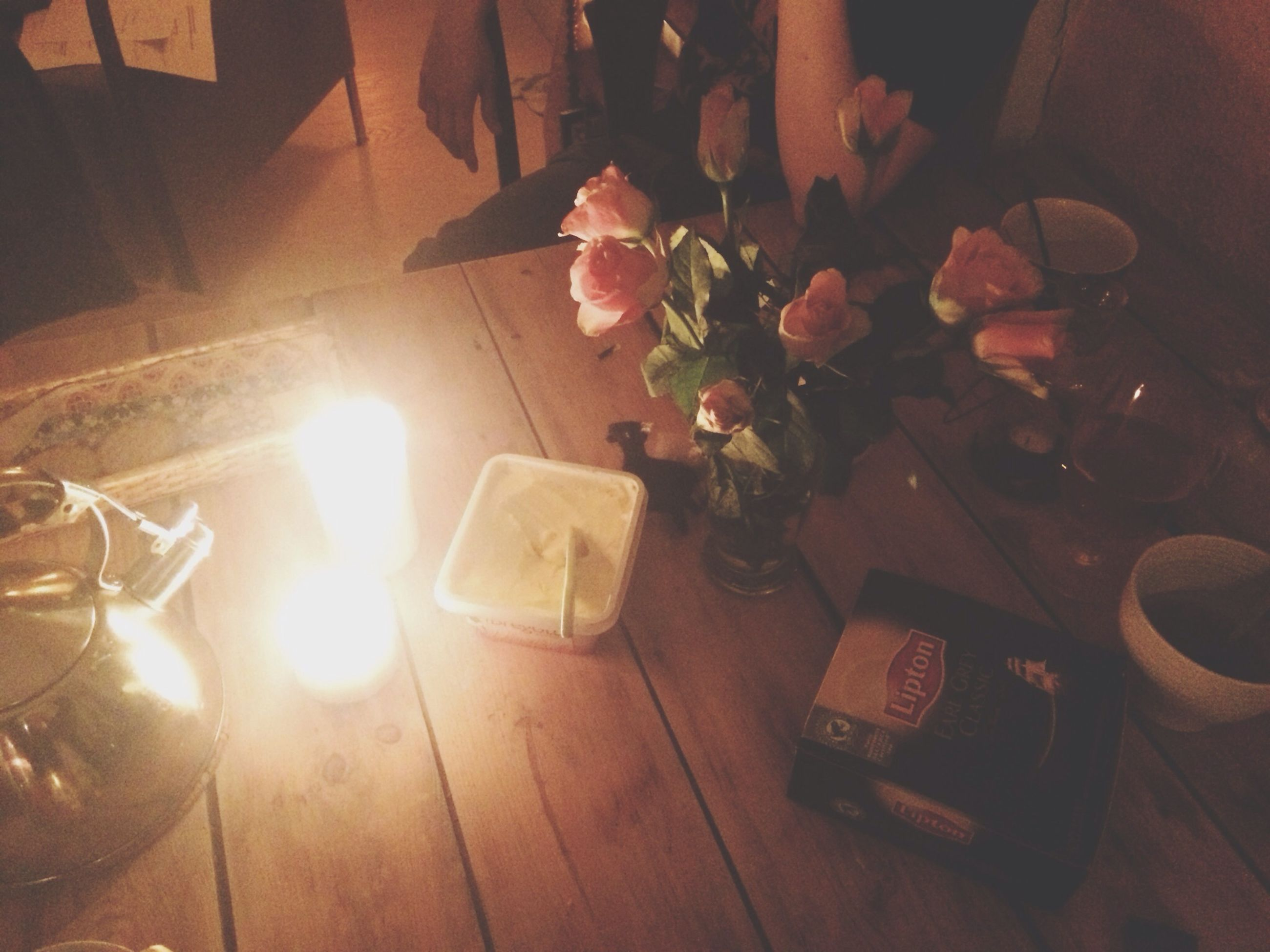 indoors, table, flower, vase, candle, home interior, illuminated, high angle view, decoration, still life, close-up, wood - material, no people, burning, freshness, lighting equipment, light - natural phenomenon, glowing, glass - material, flame