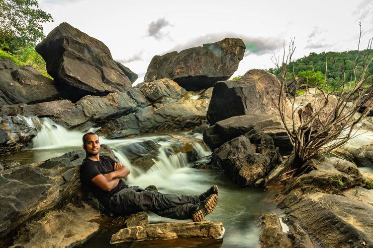 Portrait of man sitting on rock against sky