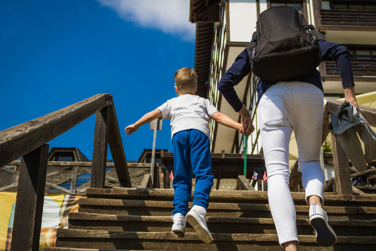 Low angle view of father and son walking on staircase