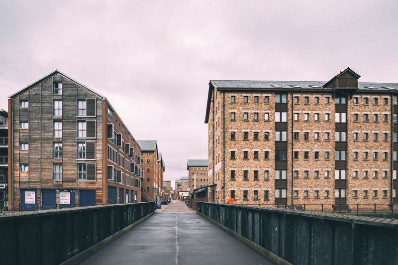 Empty footbridge by buildings against sky