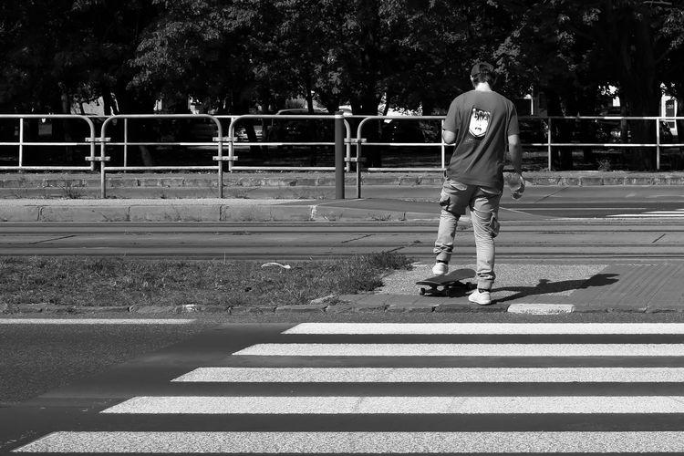 Rear view of man crossing road