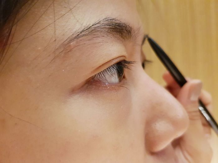 Close-up of young woman applying eyeliner