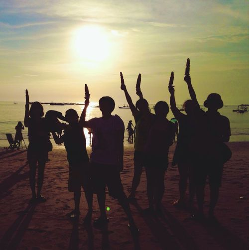 Group of silhouette children standing on beach