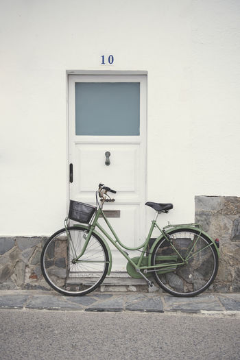vintage green bicycle in front of the door in a Spanish village Absence Architecture Bicycle Building Exterior Built Structure City Day Door Entrance Land Vehicle Mode Of Transportation No People Outdoors Road Stationary Transportation Wall Wall - Building Feature Wheel White Color
