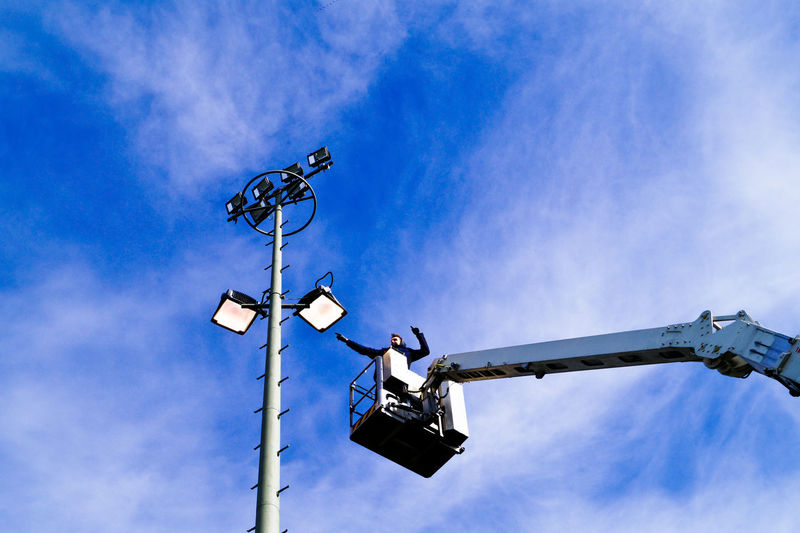 Maintenance engineer on cherry picker reaching towards floodlight