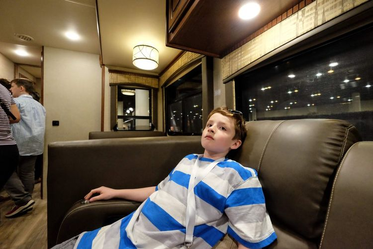 Boy looking away while sitting on seat in illuminated room