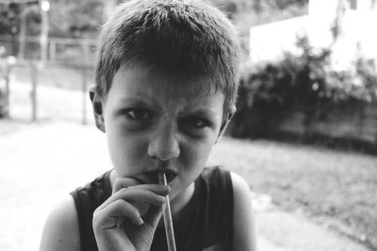Close-up portrait of boy with drinking straw in mouth