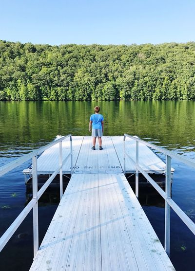 Rear View Of Boy Standing On Jetty