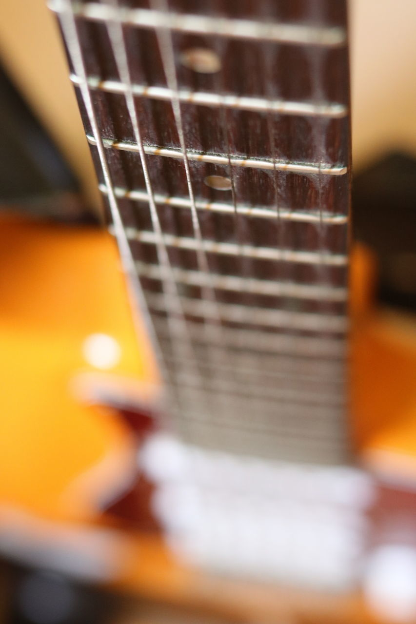 music, musical instrument, selective focus, arts culture and entertainment, guitar, fretboard, musical instrument string, indoors, string instrument, close-up, no people, electric guitar, day