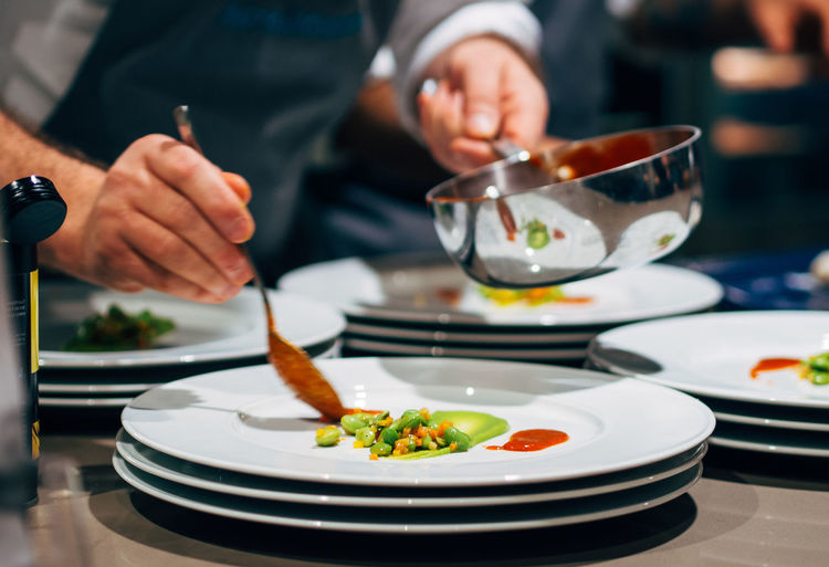 Midsection of chef garnish food in restaurant