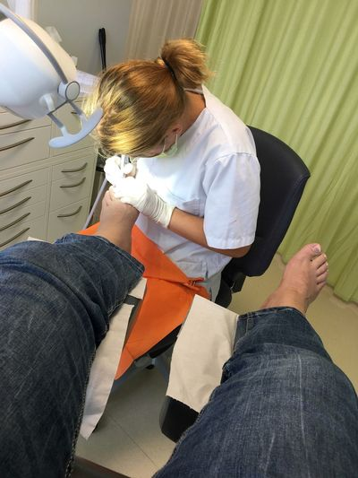 Female Doctor Examining Male Patient Foot In Clinic