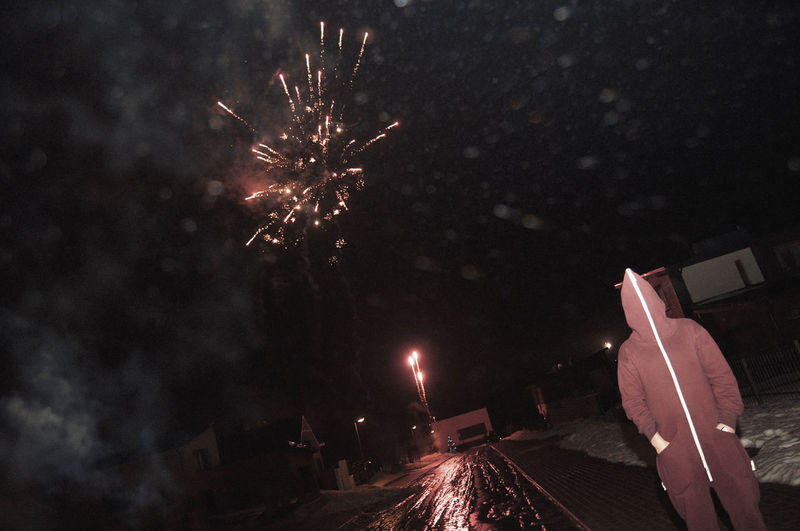Person on street under firework display at night