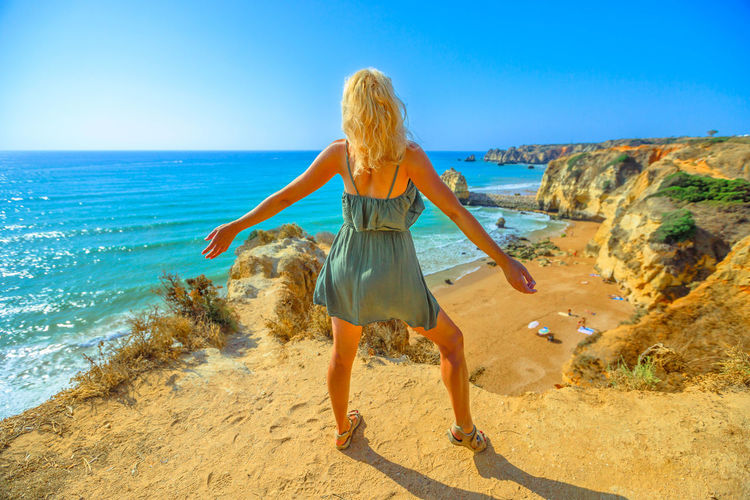 Rear View Of Woman Standing On Cliff Against Sea