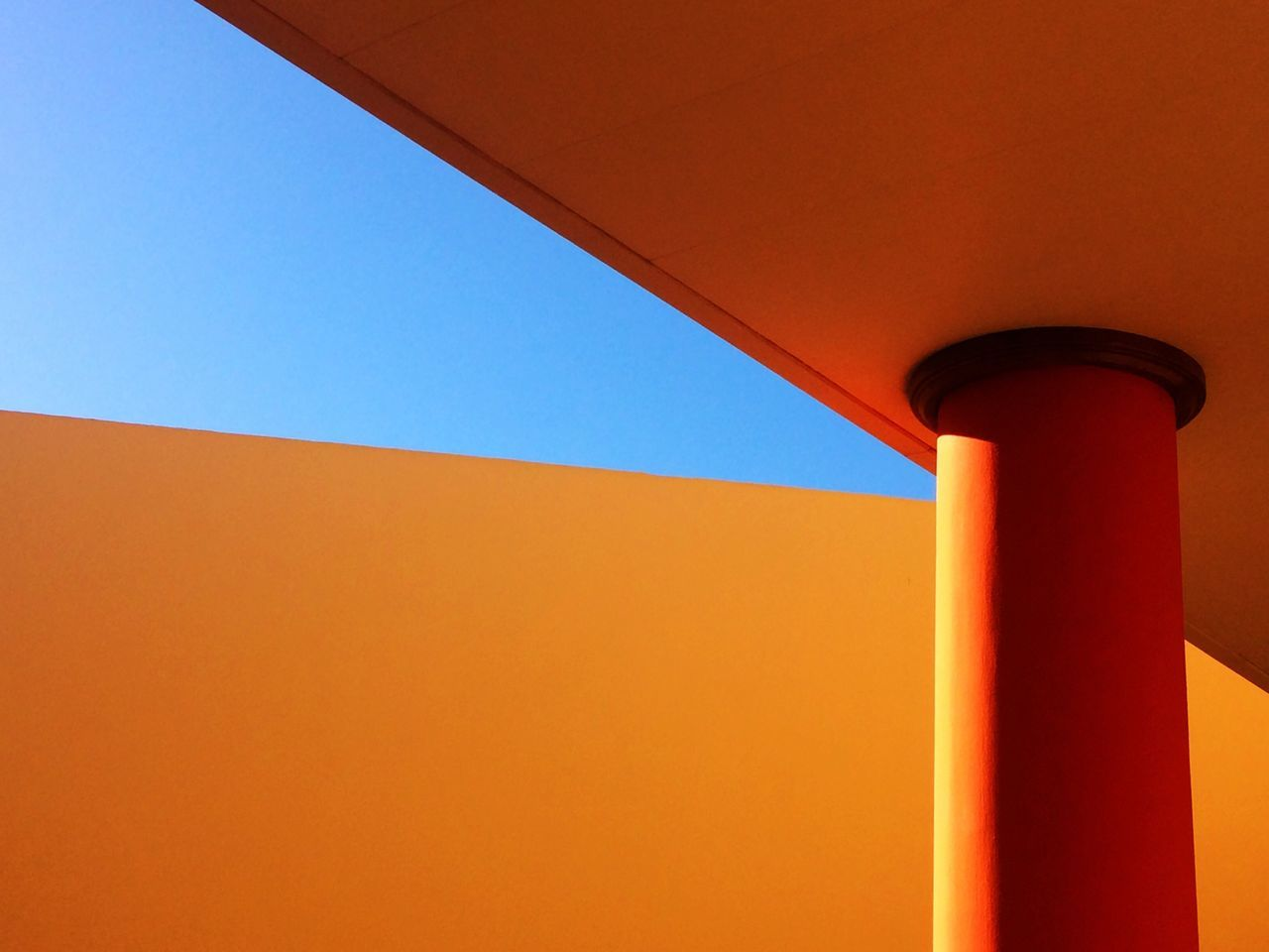 LOW ANGLE VIEW OF ORANGE BUILT STRUCTURE AGAINST CLEAR SKY
