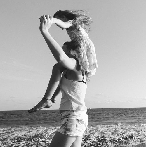 Side View Of Woman Carrying Daughter On Shoulder At Beach