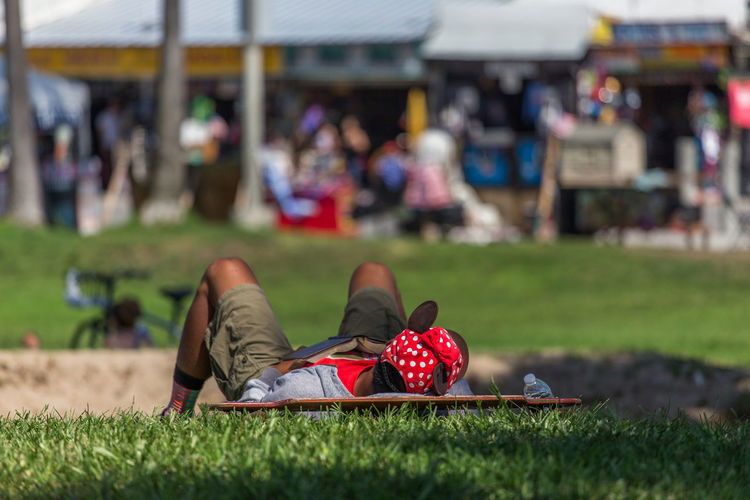 Guy taking a nap, Venice beach Los Angeles Grass Day Incidental People Focus On Foreground Real People Leisure Activity Outdoors Men Selective Focus Close-up Human Leg Venice Beach Los Angeles, California California Chilling Out Skateboard Lying Down Taking A Nap Take A Break
