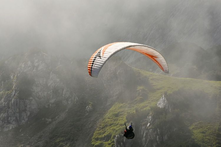 High Angle View Of Man Paragliding Against Mountains