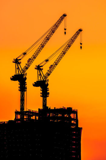 Low Angle View Of Silhouette Cranes At Construction Site Against Sky During Sunset