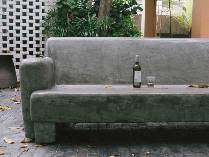Beer Bottle And Disposable Glass On Bench