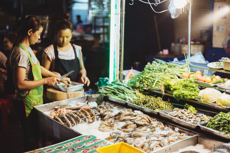 Night market Customer  Food Food And Drink Healthy Eating Market Market Stall Night Occupation People Real People Retail  Small Business Standing Two People Variation Vegetable Working Young Adult Young Women
