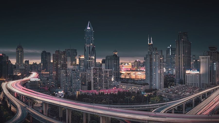 High angle view of illuminated highway amidst buildings in city at night