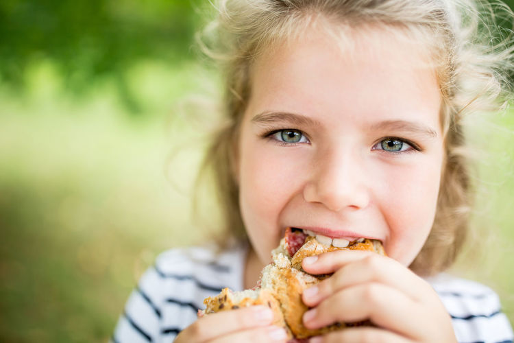 close-up portrait of girl eating BAP Biscuit Bite Off Blond Hair Bun Cake Child Childhood Close-up Day Delicious Eat Eating Focus On Foreground Food Food And Drink Fun Garden Girl Girls Hair Hairstyle Happy Headshot Holding Hunger Hungry Innocence Lifestyles Looking At Camera Luck Mouth Nature Nutrition One Person People person Portrait Pre-adolescent Child Real People Smile Snack Summer Women Young